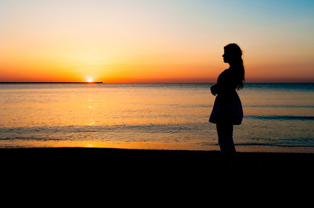 Silhouette of woman watching the sunrise