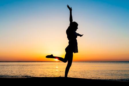 Silhouette der Frau springen in der Luft am Strand bei Sonnenaufgang.