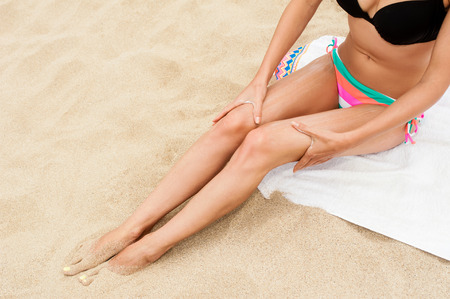 tanned body: Woman moisturizing applying sun cream on her tanned body and legs. Stock Photo
