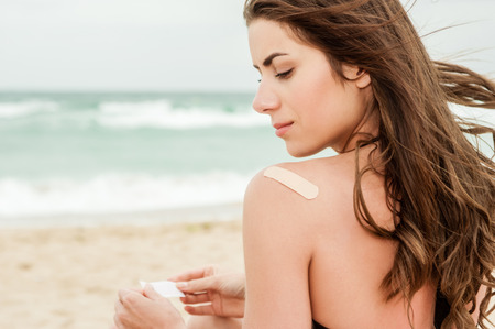 Woman at the beach with a on bandage her upper back. Stock Photo
