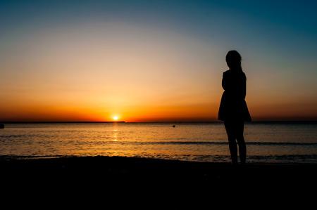 mujer sola: Mujer en traje de verano de pie en una playa de arena y mirando al sol Foto de archivo