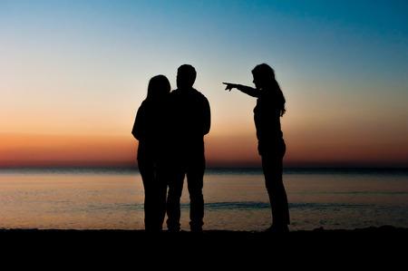 gente saltando: Silueta de la pareja y un amigo de la ma�ana en la playa y una de ellas apunta hacia la salida del sol. Textuales, juntos, ganar, ayuda, concepto de la libertad.