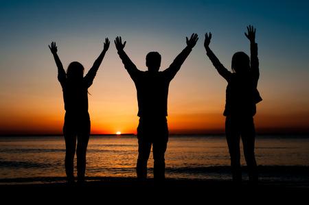 Silhouette von drei Freunden am Morgen am Strand wartet auf den Sonnenaufgang. Gewinnen, Freiheitskonzept.