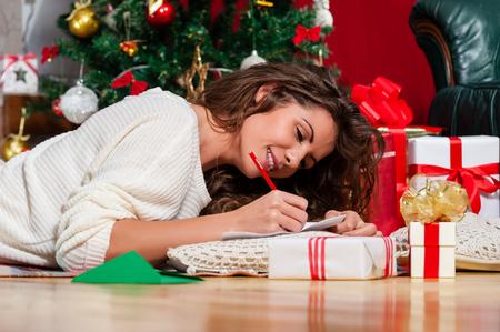 Schöne junge Frau liegt auf dem Teppich mit einem roten Stift schriftlich eine Weihnachtskarte Weihnachtsgeschenke vor Baum über Wohnzimmer