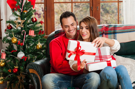 young tree: Celebrating Christmas together. Beautiful young couple sitting on the couch and smiling at camera exchanging gifts.