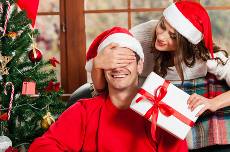 Surprise! Handsome young man sitting on the couch and holding a gift box while her girlfriend standing behind him and covering his eyes with hands and wering santa hat
