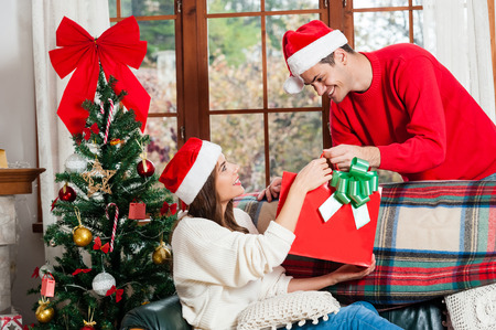 Lover offering present for christmas wering santa hat. Christmas tree background.