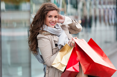 gift bags: Photo of young joyful woman with shopping bags on the background of shop windows. Outdoors.