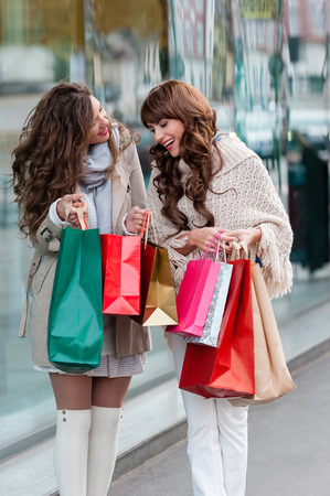 christmas shopping bag: Two beautiful women looking inside shopping bags in the city over shop windows background