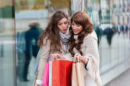 navidad elegante: Dos atractivas mujeres jóvenes de compras juntos, con sus bolsas de compra, sonriendo, mientras está de pie delante de la ventana de la tienda. Aire libre.