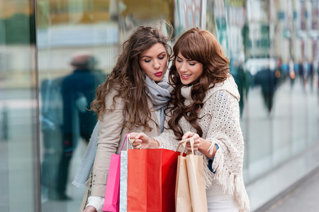 elegant christmas: Two attractive young women shopping together,holding shopping bags,smiling, while standing in front of shop window. Outdoors.