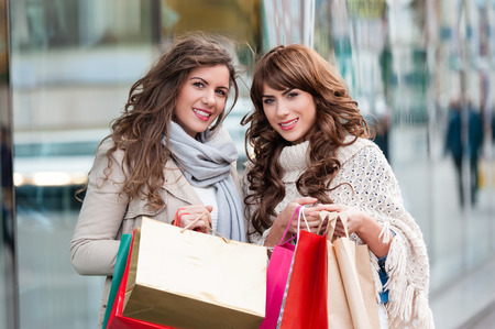 gift bags: Two attractive young women shopping together,holding shopping bags,smiling, while standing in front of shop window. Outdoors.