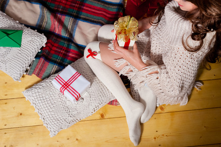 young tree: Close-up of young woman legs holding gift box, lying on carpet at the Christmas tree over living room.