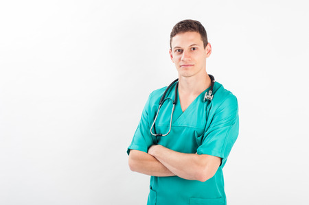 Medical portrait. Male nurse or young man doctor smiling happy and proud in blue scrubs isolated on white background. Young caucasian male medical professional. Stockfoto