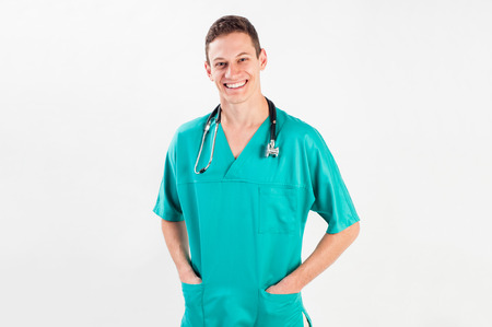 Medical portrait. Male nurse or young man doctor smiling happy and proud in blue scrubs isolated on white background. Young caucasian male medical professional. Standard-Bild