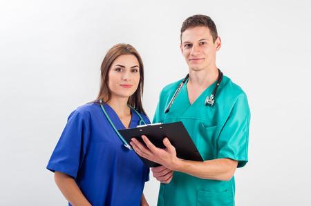 Medizinische Fachleute stehen isoliert. Junge kaukasisch Mann und junge Frau Krankenschwester in der medizinischen scheuert Standard-Bild