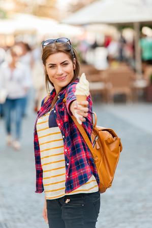 Frau essen Eis auf Urlaubsreisen. Smiling Mädchen Spaß essen Eis im Freien während der Ferien in Europa.