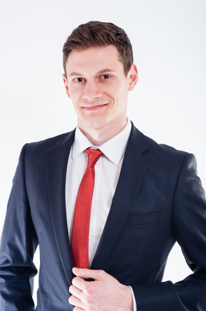 careerist: Portrait of young smilling businessman in black suit and red tie Stock Photo