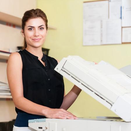 Pretty young woman using a copy machine Stockfoto