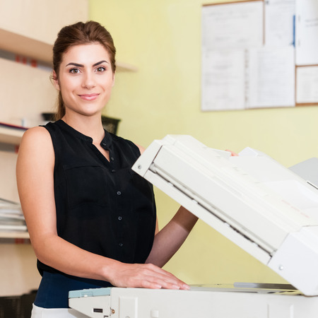 Pretty young woman using a copy machine Stock fotó