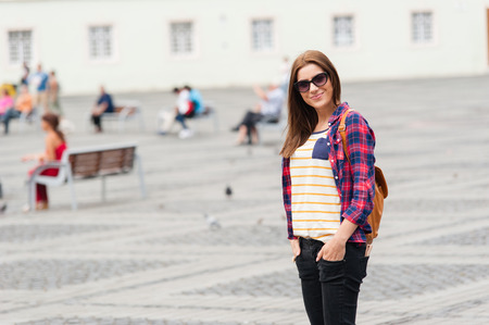 youthfulness: Young attractive woman visit city,smiling and posing in a sunny day. Beautiful medieval Romania, Sibiu.