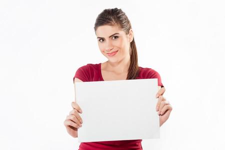hoja en blanco: Chica mantenga el papel en blanco blanco. Demostración de la mujer sonriente tarjeta en blanco joven. Retrato de la muchacha aislado en el fondo blanco.