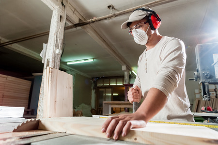 ear protection: Carpenter working on wood machine in factory