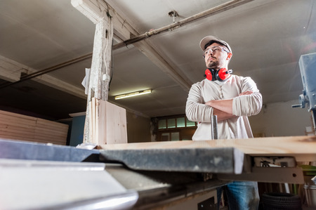 hearing protection: Carpenter working with Industrial tool in wood factory wearing safety glasses and hearing protection. Stock Photo
