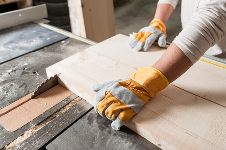 carpintero: Carpintero que trabaja con la herramienta industrial en la fábrica de madera, lámina circular con un tablero de madera