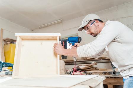 carpintero: Carpintero que trabaja el montaje de un cajón con un destornillador, él lleva gafas de seguridad de protección