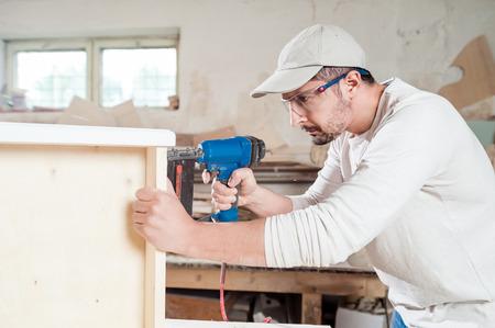 planos electricos: Carpintero que trabaja el montaje de un cajón con un destornillador, él lleva gafas de seguridad de protección
