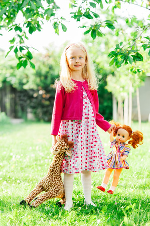 3 4 years: Cute little girl holding her favorite giraffe toy, in the park.