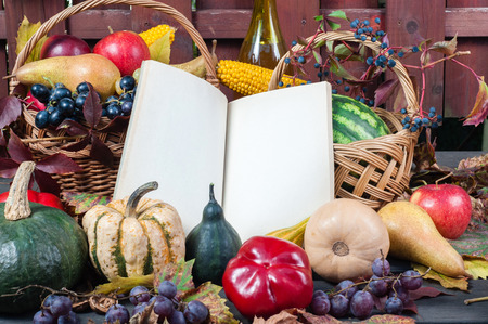 decorate notebook: Autumn and Thanksgiving concept. Seasonal fruit and pumpkins in basket on wood background with open old book to place your text.