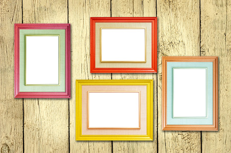 colorful frame: Four multicolored photo frames on the retro wood wall