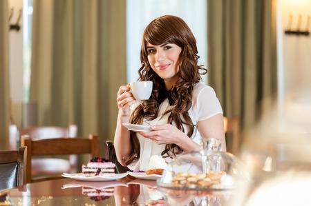 Porträt der jungen hübschen lächelnden Frau, die Fruchtkuchen und Kaffee am Kaffeekuchenshop genießt