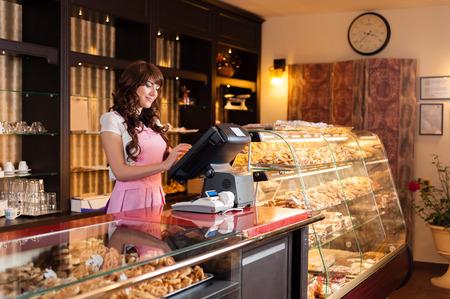 ケーキ屋で幸せな若い笑顔売り手