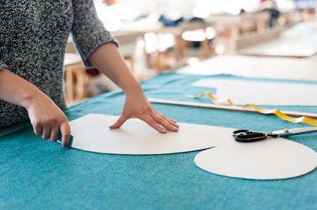 mujeres fashion: Diseñador de moda femenina trabajando con bocetos en estudio y eligiendo el paño Foto de archivo