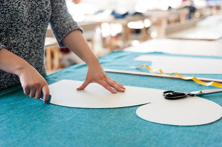 Female fashion designer working with sketches at studio and choosing cloth Standard-Bild
