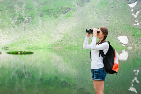 balea: Young woman admiring the beautiful view of the lake and mountains, holding a binocular. Scene from Balea Lake, Romania.