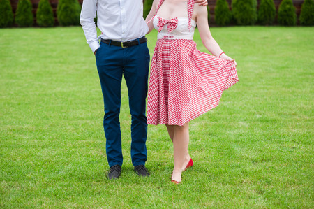dress up: Couple in the grass, only legs, engagement photo, before wedding, picnic, sunny day, romantic photo, without face, girl with pin up dress, vintage color