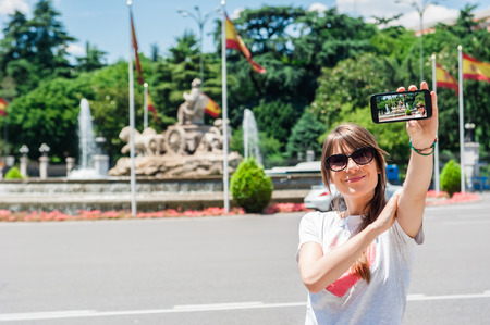 palacio de comunicaciones: Young tourist woman taking picture with Cibeles Fountain, one of the most famous monuments of architecture of Madrid located on the Cibeles square in the Centre of Madrid, Spain
