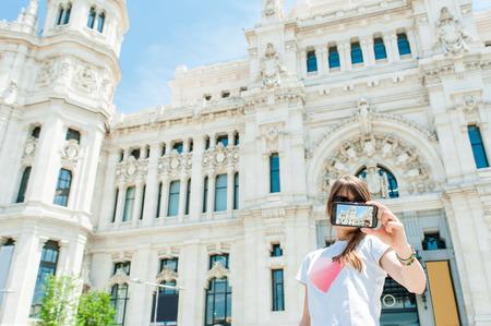 palacio de comunicaciones: Young tourist woman taking picture in front of Palacio de Comunicaciones located on the Cibeles square in the Centre of Madrid, Spain