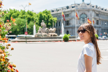 Young tourist woman in front Cibeles Fountain, one of the most famous monuments of architecture of Madrid located on the Cibeles square in the Centre of Madrid, Spain Stock fotó