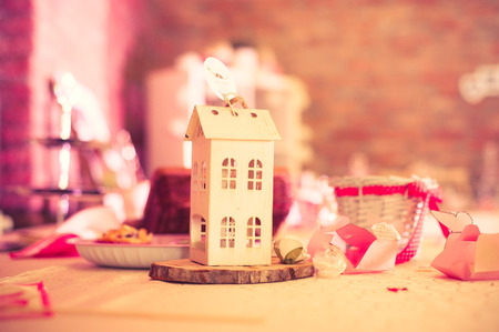 small paper: Decorative small paper house at a wedding reception.