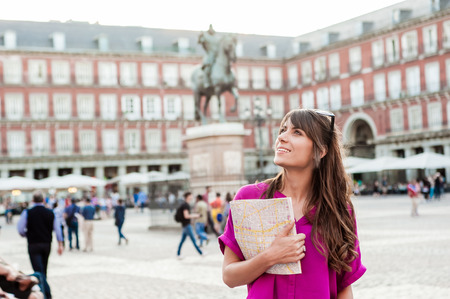 Young woman tourist holding a paper map in Plaza Mayor square, Madrid, Spain, looking at buildings. Tourist attraction, statue of Felipe III in the background. Stockfoto