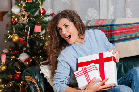 fire place: Happy young woman sitting on couch holding christmas present boxes next to christmas tree and fire place