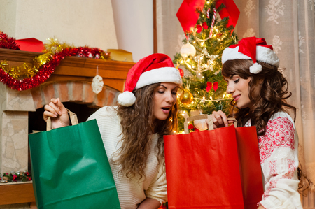 female christmas: Christmas holiday happy girl friends exploring bags after shopping in christmas decorated living room ,wear red new year santa hat, over chimney and christmas tree colorful lights background Stock Photo