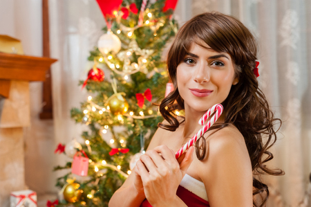 guilty pleasures: Pretty young woman in red and white christmas dress and long beautiful hair, holding a christmas candy stick , near chimney and Christmas tree, over living room..