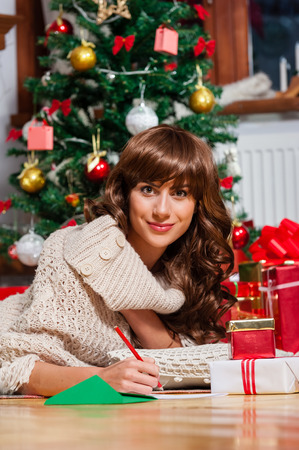female christmas: Beautiful young woman lying on carpet with a red pen writing a christmas card  Christmas presents in front of tree over living room Stock Photo