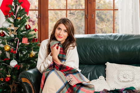 Young woman sitting on couch, alone, holding a blanket ,over christmas tree background on living room
